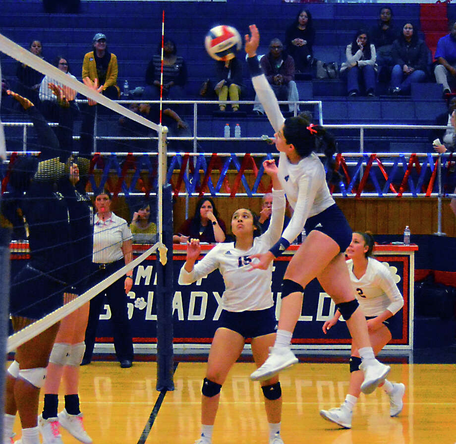 Plainview Lady Bulldog Alexa Hinojos (middle) uses a set from Christen Gonzalez (15) for a hit over Lubbock Lady Westerners Clarissa Francis (left) and Kennedy Schepler (pink laces) during a District 3-5A volleyball match on Tuesday night in Plainview. Lady Bulldog Aspin Miller (far right) comes in to help on the potential block. Photo: Alexis Cubit/Plainview Herald