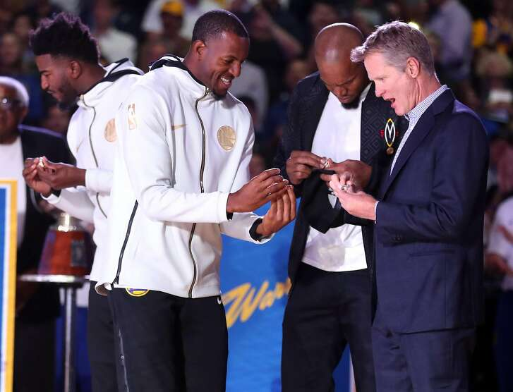 Golden State Warriors' head coach Steve Kerr, Andre Iguodala nd former Warriors, David West, look at their 2018 NBA Championship rings during a ceremony before Opening Night game against Oklahoma City Thunder at Oracle Arena in Oakland, Calif. on Tuesday, October 16, 2018.