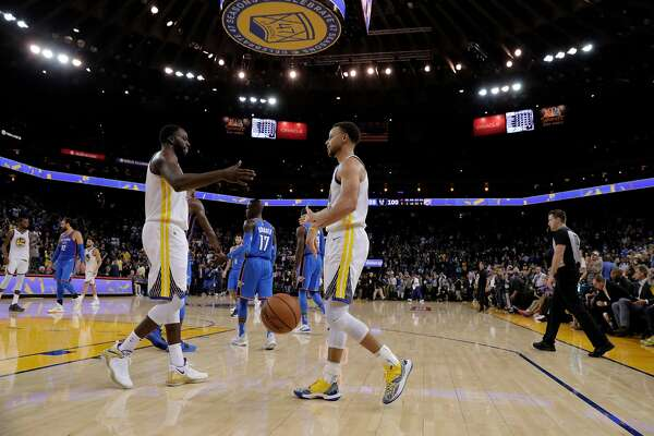 Stephen Curry (30) and Draymond Green (23) high five after the clock expired as the Golden State Warriors played the Oklahoma City Thunder at Oracle Arena in Oakland, Calif., on Tuesday, October 16, 2018. The Warriors received their 2018 NBA Championship rings and saw their championship banner raised in the arena before the game. The Warriors defeated the Thunder 108-100.