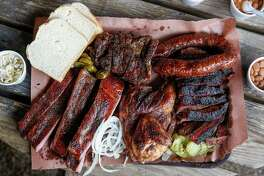 Smoked brisket, pork steak, chicken, ribs and sausage fill a platter at Snow's BBQ Saturday, March 24, 2018 in Lexington.
