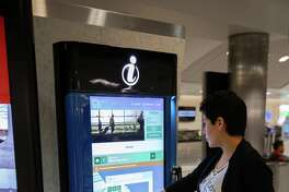 A woman illustrates how to use new interactive kiosks now available at Bush Intercontinental and Hobby airports.