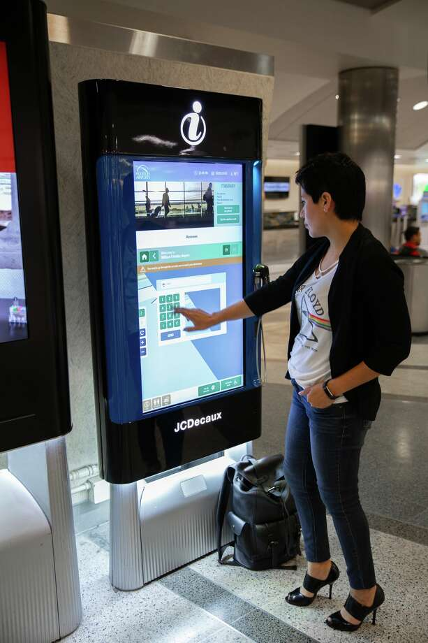 A woman illustrates how to use new interactive kiosks now available at Bush Intercontinental and Hobby airports.  Keep going to see where Houston airports rank in the J.D. Power 2018 North America Airport Satisfaction Study. Photo: Houston Airport System