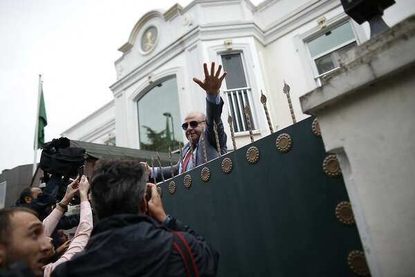 A security guard asks members of the media to back off, after rushing to cover the arrival of a group of a Saudi delegation that walked in the Saudi Arabia consul's residence in Istanbul, Wednesday, Oct. 17, 2018. Turkey's interior minister says his country is waiting for a final permission from Saudi Arabia to search the residence as part of an investigation into the disappearance of journalist Jamal Khashoggi. (AP Photo/Emrah Gurel)