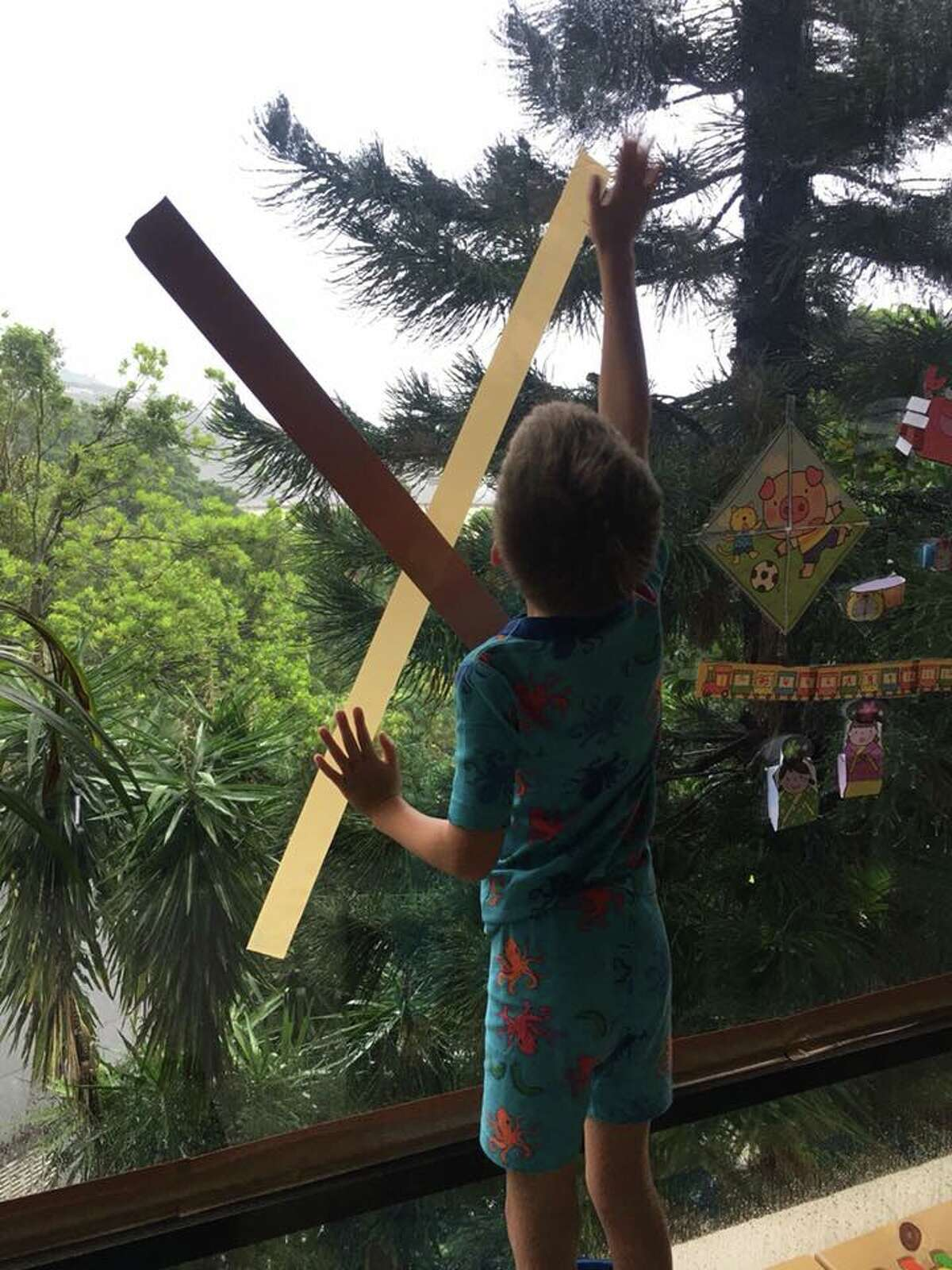 Knapp's grandson Cooper helping tape up windows before Typhoon Mangkhut arrives in Hong Kong.