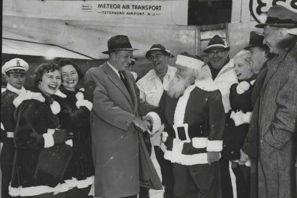 "Santa Claus came to town yesterday - in a DC-4 which set down at Albany Airport, New York. He was in Albany for the seventh ""Operation Toylift"" which brings toys for needy children from Santa's Workshop at North Pole, New York. Here Santa Claus is being welcomed by Mayor Corning. At left are Joan and Mary Rice, gnomes for the day. Behind Santa is Wes Keppel of Esso Standard Oil, which supplied the plan for St. Nick. December 3, 1955 (Knickerbocker News Staff Photo/Times Union Archive)"
