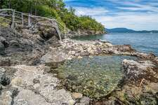 This artisiic and private property enjoys almost one full acre of Lopez Island waterfront, asking $849K