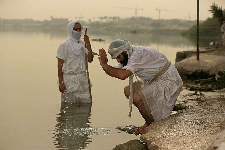 Followers of the Mandaean religious sect perform rituals alongthe Tigris River reserved for them, in Baghdad. The faith holds that only flowing water can baptize the faithful. Photo: Hadi Mizban / Associated Press