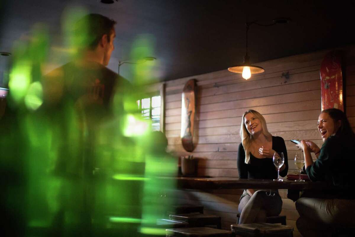 Emma Scholey and Jamie Campisano chat with John Dampeer of Fool's Errand as empty beer bottles catch the light in the foreground.