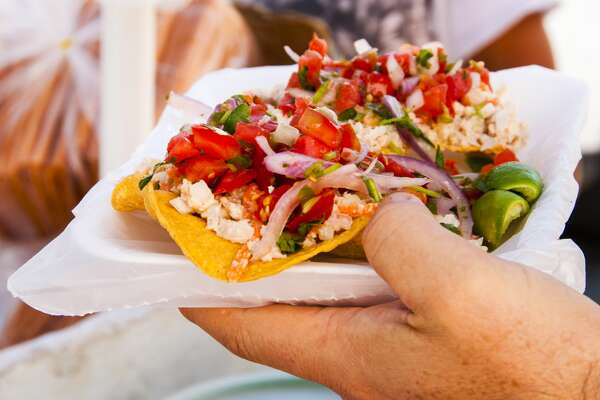Close-up of hand holding taco purchased from street vendor in the Romantic Zone of Puerto Vallarta on the Bay of Banderas, Pacific coast of Mexico