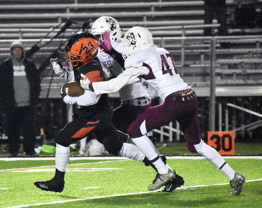 Edwardsville running back Dionte Rodgers splits two Belleville West players on his way to a big gain in the fourth quarter on Friday in Edwardsville. Photo: Matt Kamp/Intelligencer