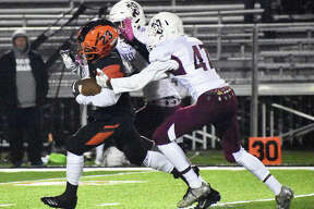 Edwardsville running back Dionte Rodgers splits two Belleville West players on his way to a big gain in the fourth quarter on Friday in Edwardsville.