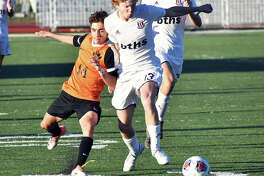 Edwardsville midfielder Jakob Doyle, left, battles for possession against a Belleville West player during the first half of Tuesday's regional semifinal in O'Fallon.