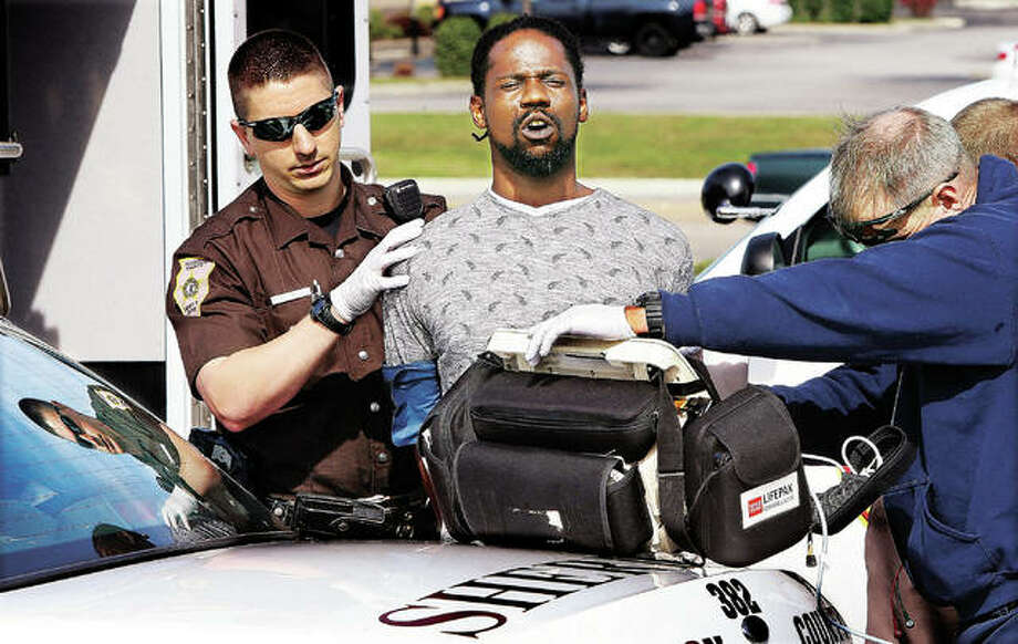 """Madison County Sheriff's deputy Benjamin Patterson, left, keeps a firm grip on Donald M. Nelson after his arrest Tuesday in connection with the murder of Eldon """"Twirp"""" Williams in the 200 block of West Delmar Avenue in Alton. Alton Fire Department paramedics, right, were checking the suspect's vital signs after he claimed he was ill. He was transported by ambulance to a local hospital. Officials announced Wednesday at a press conference that Nelson is facing multiple charges related to the shooting, including three first-degree murder charges. Photo: John Badman 