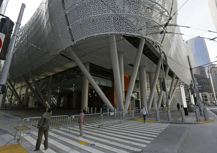 FILE - In this Sept. 27, 2018, file photo, people stop to look at the closed Salesforce Transit Center in San Francisco. San Francisco officials say they plan to re-open a street shuttered last month because of cracks found in the new $2 billion transit terminal. Mark Zabaneh, executive director of the Transbay Joint Powers Authority, said Friday, Oct. 5, they will open Fremont Street for the morning commute Oct. 12. (AP Photo/Eric Risberg, File)