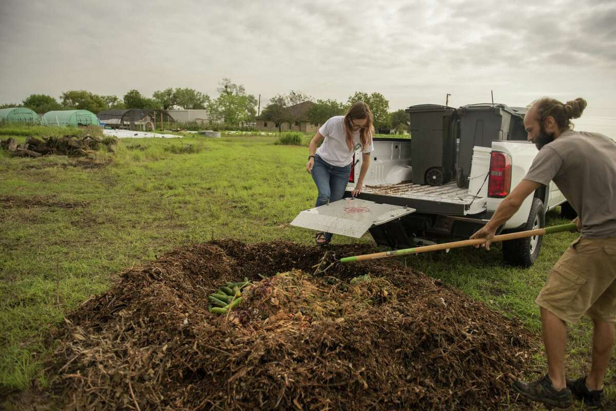 Kate Gruy Jaceldo, co-owner of the Compost Queens, and farmer Sylvain Clavieres prepare a compost mound om his farm after a shipment of fresh food scraps.