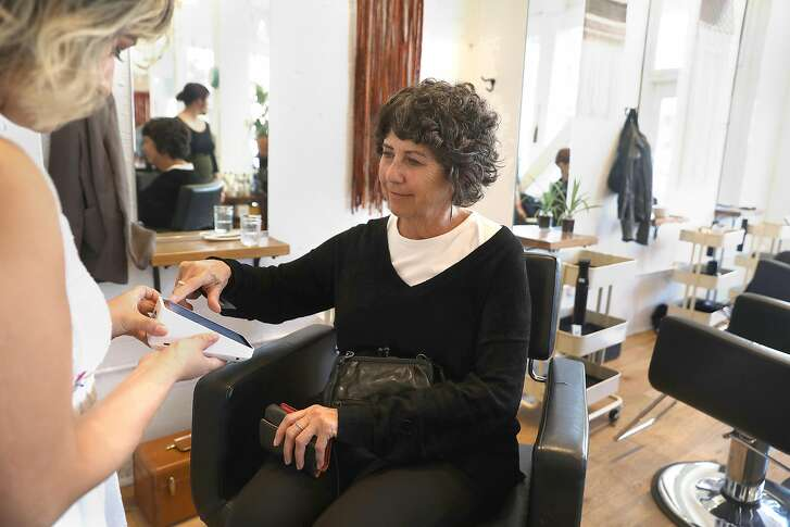 Customer Cindy Morton from San Francisco pays her haircut on the new portable Square tablet at Edo salon on Wednesday, Oct. 17, 2018, in San Francisco, Calif.  Square announces their new hardware--a portable tablet register that can be brought to customers to pay for a service.