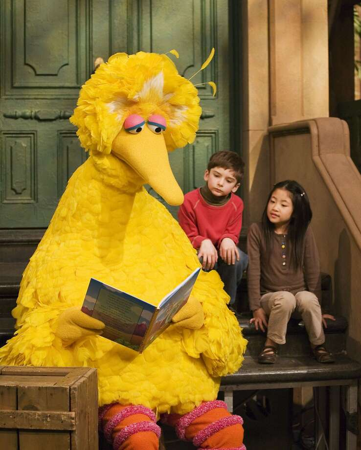 "FILE - In this April 10, 2008 file photo, muppet character Big Bird reads to Connor Scott and Tiffany Jiao during a taping of  the children's program ""Sesame Street"" in New York. Sesame Street continues to attract millions of viewers after 45 years on the air, appealing to both preschoolers and their parents with content that is educational and entertaining. The show has kept up with the times by making its segments faster-paced, by fine-tuning messages, and by keeping a steady flow of appearances by contemporary celebrity guests. The show first aired Nov. 10, 1969. (AP Photo/Mark Lennihan, File) Photo: MARK LENNIHAN, Associated Press"