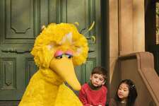 """FILE - In this April 10, 2008 file photo, muppet character Big Bird reads to Connor Scott and Tiffany Jiao during a taping of the children's program """"Sesame Street"""" in New York. Sesame Street continues to attract millions of viewers after 45 years on the air, appealing to both preschoolers and their parents with content that is educational and entertaining. The show has kept up with the times by making its segments faster-paced, by fine-tuning messages, and by keeping a steady flow of appearances by contemporary celebrity guests. The show first aired Nov. 10, 1969. (AP Photo/Mark Lennihan, File)"""