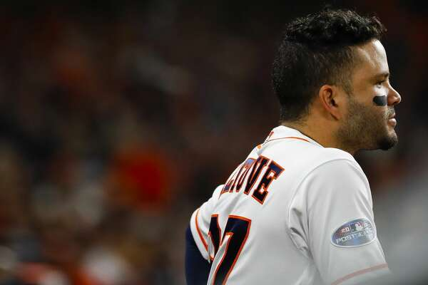 Houston Astros designated hitter Jose Altuve (27) watches from the dugout while his team plays in the top of the eighth inning of Game 3 of the American League Championship Series at Minute Maid Park on Tuesday, Oct. 16, 2018, in Houston.