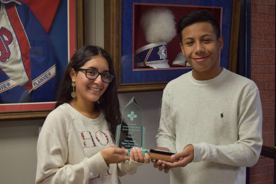 Serena Lopez, PHS junior, clarinet player and drum major, and Peter Guajardo, PHS senior, trombone player an drum major, showcased the band's trophies from the weekend's competition as other band members, including the other three drum majors, practiced outside Wednesday morning. Photo: Ellysa Harris/Plainview Herald