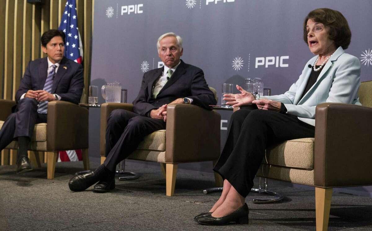 State Sen. Kevin de León (left) and moderator Mark Baldassare listen to U.S. Sen. Dianne Feinstein during the debate in S.F.