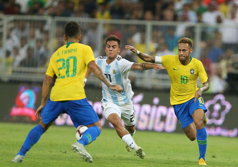 Neymar trata de quitarle la pelota a Paulo Dybala durante la victoria de Brasil sobre Argentina por 1-0 en Arabia Saudita. Photo: AFP/Getty Images