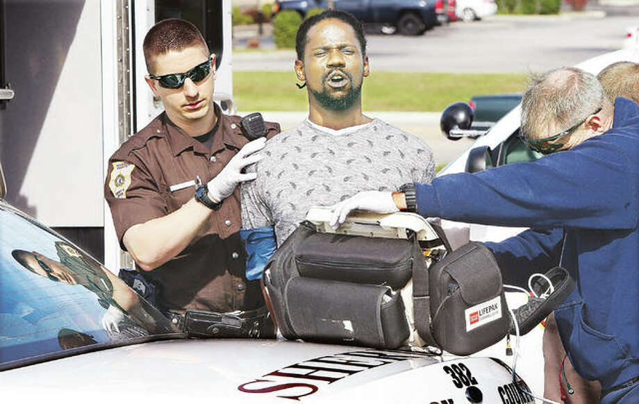 """Madison County Sheriff's deputy Benjamin Patterson, left, keeps a firm grip on Donald M. Nelson, 34, center, after his arrest Tuesday in connection with the murder of Eldon """"Twirp"""" Williams in the 200 block of West Delmar Avenue in Alton. Alton Fire Department paramedics, right, were checking the suspect's vital signs after he claimed he was ill. He was transported by ambulance to a local hospital. Officials announced Wednesday at a press conference that Nelson has been charged with three counts of first-degree murder and five other felonies in the shooting death of the 87-year-old Williams. Photo: John Badman 