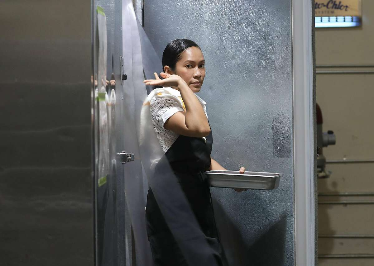 Chef/owner Siska Silitonga Marcus of Chili Cali gets ingredients from the refrigerator to make a small batch of her sambal sauce on Friday, Sept. 7, 2018, in San Francisco, Calif.