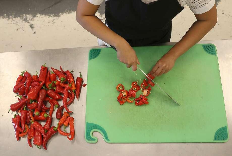 Chef/owner Siska Silitonga Marcus of Chili Cali cuts chili for her sambal sauce on Friday, Sept. 7, 2018, in San Francisco, Calif. Photo: Liz Hafalia / The Chronicle