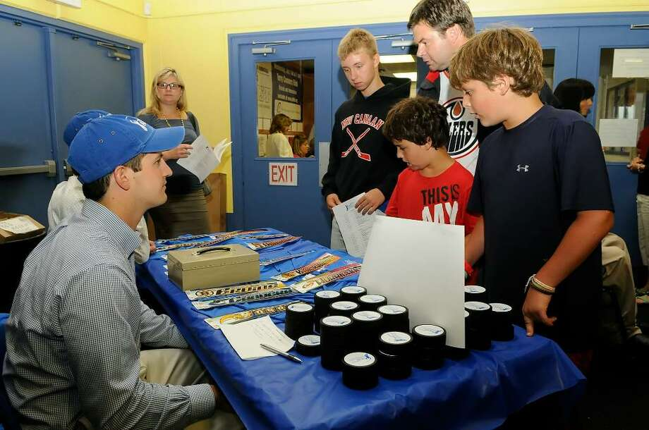 Brothers Colin Bella, 9 (red shirt) and AJ Bella, 11 (blue shirt) look over the offerings at a vendor table at Terry Connors Rink in Stamford on July 14, 2010. The Bella brothers, Norwalk, were among the fans gathering for an exhibition hockey game featuring NHL, AHL, and college players for the second annual Big Assist, to benefit the Obie Harrington-Howes Foundation. The foundation assists those that need help because of spinal injury or disease. Additional activites planned for the evening include a skills competition and a silent auction. Photo: Shelley Cryan / Shelley Cryan