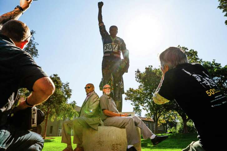 Tommie Smith (left) and John Carlos sit below the statue that honors their iconic protest at the 1968 Mexico City Olympics.