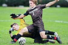 Brunswick's Harry Barringer, center, plays a rebound off a block by Salisbury goalie Jonah Anderson during the boys high school soccer match between Brunswick School and Salisbury School at Brunswick in Greenwich, Conn., Wednesday, Oct. 17, 2018. Barringer did not score on his shot attempt.