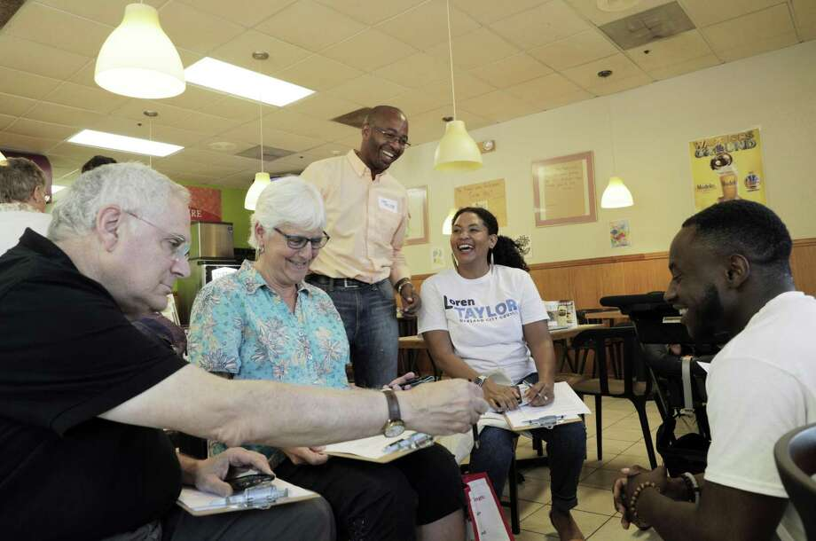 Loren Taylor (standing) chats with campaign volunteers, Dave Boitano (left), Valerie Stoller and Rhea Bailey, and campaign coordinator De'Zhon Grace before heading out to campaign in Oakland's Ridgemont neighborhood. Photo: Carlos Avila Gonzalez / The Chronicle / ONLINE_YES