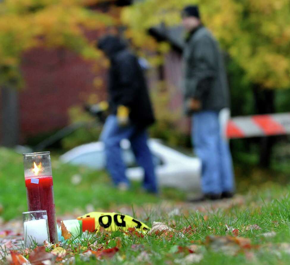 CINDY SCHULTZ/TIMES UNION -- A small memorial glows on the sidewalk as Albany detectives Victor Pizzola, left, and Mark Sauter, right, use a metal detector as they search for evidence at the crime scene on Wednesday, Oct. 22, 2008, on South Lake Street in Albany, N.Y. University at Albany student Richard Bailey was fatally shot Monday night at this site. (WITH FILKINS STORY)
