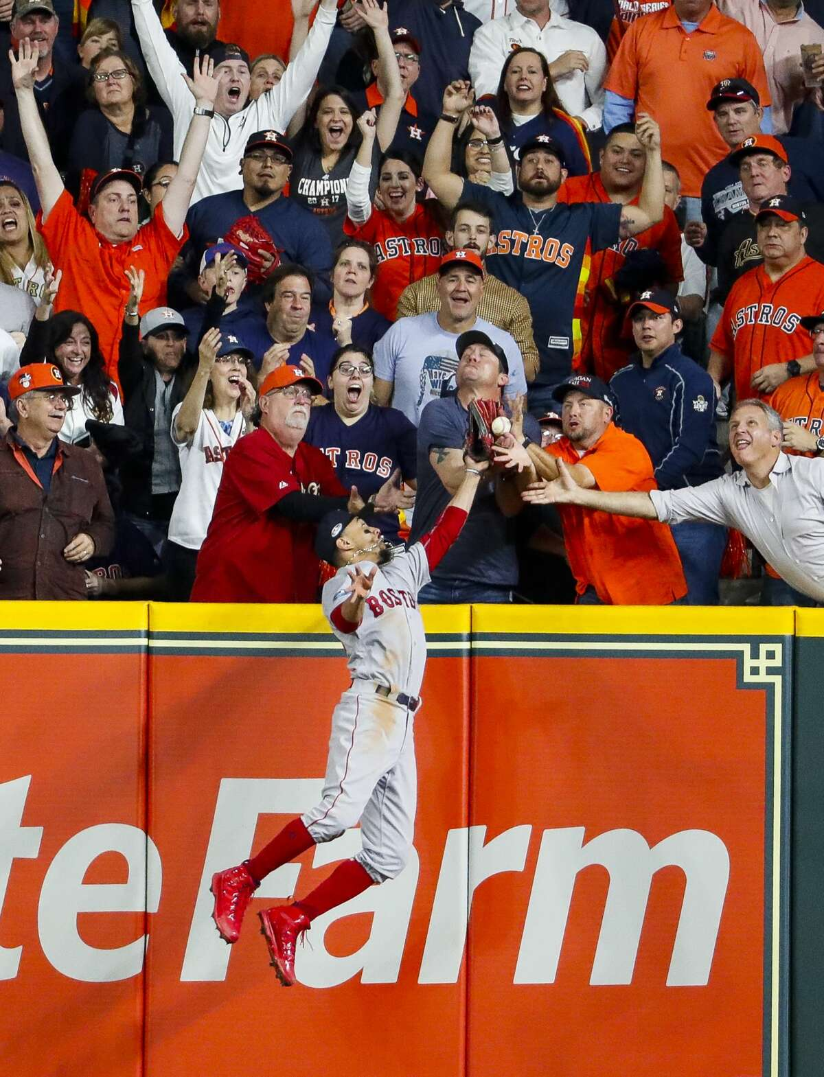 Boston Red Sox Mookie Betts (50) tries to catch a deep hit over the wall by Houston Astros designated hitter Jose Altuve (27) during the first inning of Game 4 of the American League Championship Series at Minute Maid Park on Wednesday, Oct. 17, 2018, in Houston. Altuve would be called out on the play due to fan interference.