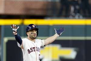 Houston Astros designated hitter Jose Altuve (27) reacts as he is called out because of fan interference from a long ball he drove over the wall in right field that Boston Red Sox Mookie Betts (50) tried to catch during the first inning of Game 4 of the American League Championship Series at Minute Maid Park on Wednesday, Oct. 17, 2018, in Houston. The play was reviewed and Altuve was called out.