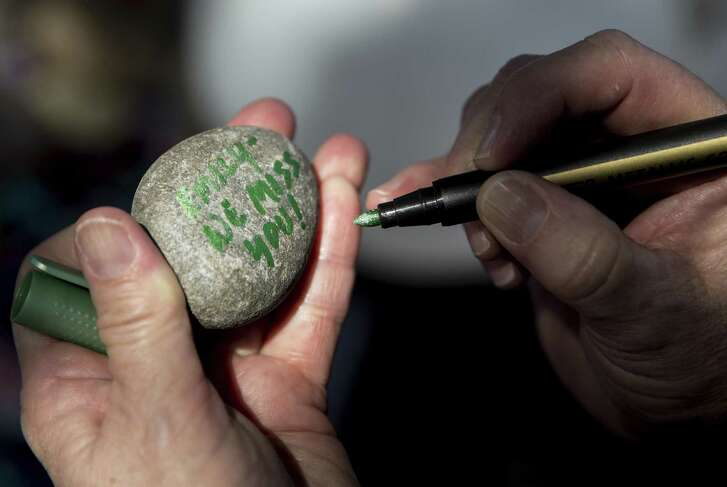 Friends and relatives of Emily Courchesne who was shot and killed in October 2017 write messages on stones in her honor during a memorial service.