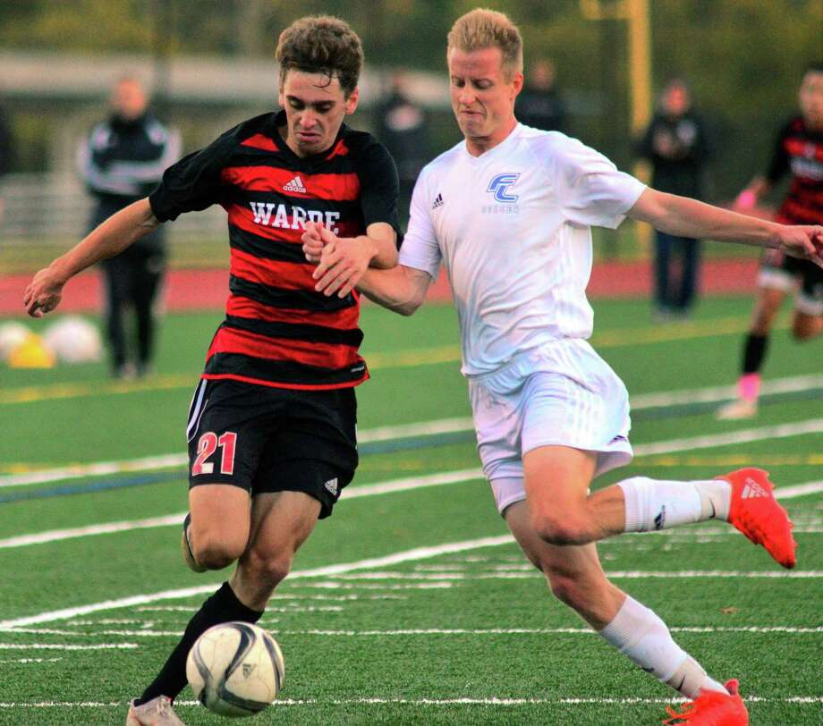 Fairfield Warde's Jake Berecz, left, and Fairfield Ludlowe's Jack Owens converge on the ball during boys high school soccer action in Fairfield, Conn., on Wednesday Oct. 17, 2018. Photo: Christian Abraham / Hearst Connecticut Media / Connecticut Post