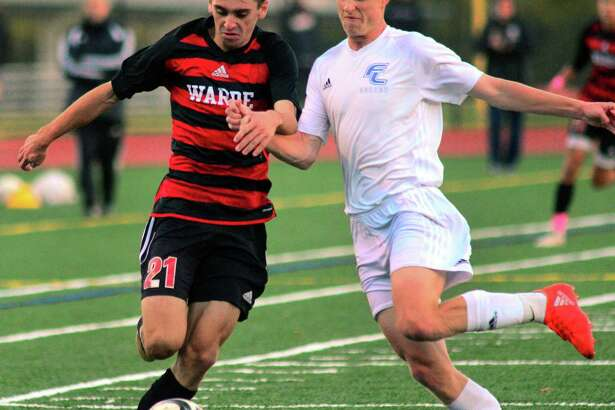 Fairfield Warde's Jake Berecz, left, and Fairfield Ludlowe's Jack Owens converge on the ball during boys high school soccer action in Fairfield, Conn., on Wednesday Oct. 17, 2018.