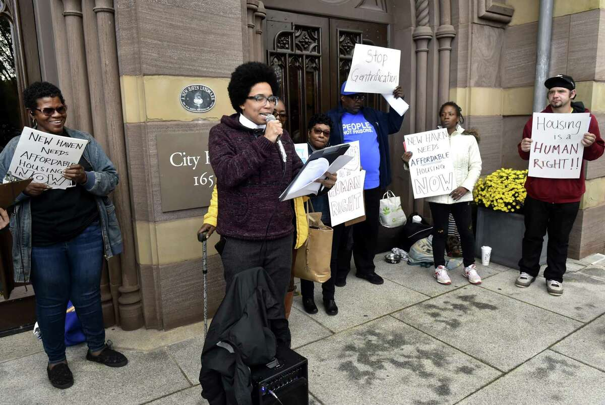 Kom Hart of Mothers & Others For Justice, left, and Kerry Ellington of the New Haven Legal Assistance Association, second from left with microphone, protest in front of New Haven City Hall Wednesday about the lack of affordable housing in New Haven.