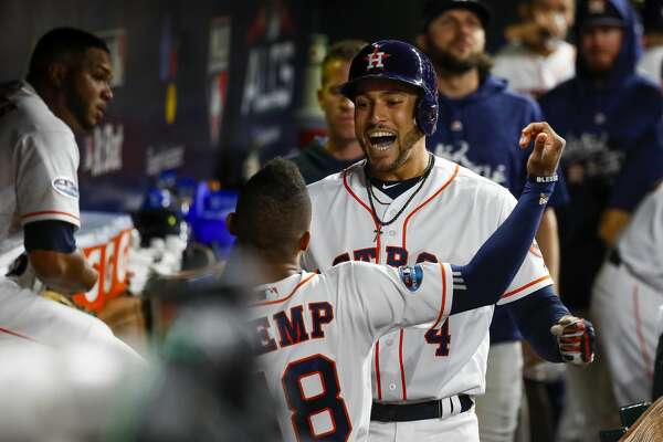 Houston Astros George Springer (4) is greeted back to the Astros dugout by Tony Kemp (18) after Springer hit a solo home run during the third inning of Game 4 of the American League Championship Series at Minute Maid Park on Wednesday, Oct. 17, 2018, in Houston.