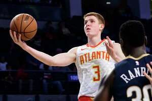 FILE - In this Oct. 1, 2018 file photo, Atlanta Hawks rookie guard Kevin Huerter (3) goes to the basket past the defense of New Orleans Pelicans forward Julius Randle during the second half of a preseason basketball game in Atlanta.  Wearable technology has been around the NBA for the past several seasons. It's not permitted on game nights, and anything specific about processes the 30 teams are using falls into the category of closely guarded secret.  Huerter said in his short time as a pro, he's learned a ton about his body that he didn't even know because of what he's gleaned off what his team has collected. (AP Photo/John Amis, File)