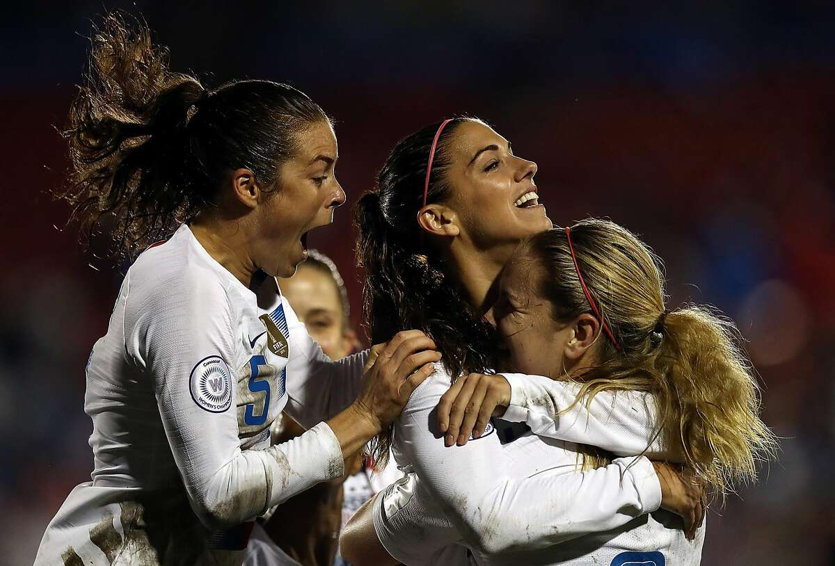 FRISCO, TX - OCTOBER 17: Alex Morgan #13, center, celebrates her goal with Kelley O'hara #5, left and Lindsey Horan #9 of the United States against Canada in the CONCACAF Women's Championship final match at Toyota Stadium on October 17, 2018 in Frisco, Texas. (Photo by Ronald Martinez/Getty Images)