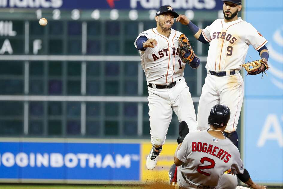 Houston Astros Carlos Correa (1) collides with Boston Red Sox Xander Bogaerts (2) after throwing out Boston Red Sox Rafael Devers (11) at first base during the seventh inning of Game 4 of the American League Championship Series at Minute Maid Park on Wednesday, Oct. 17, 2018, in Houston.