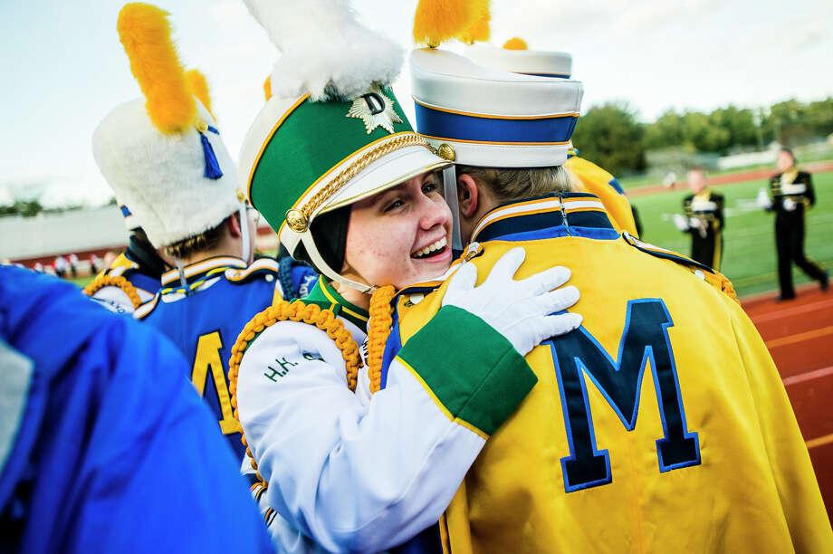 Dow senior Emma Allington, center, hugs Midland senior Grace Pardel, right, during the annual Midland Marching Band Showcase on Wednesday, Oct. 17, 2018 at Midland Community Stadium. (Katy Kildee/kkildee@mdn.net) Photo: (Katy Kildee/kkildee@mdn.net)