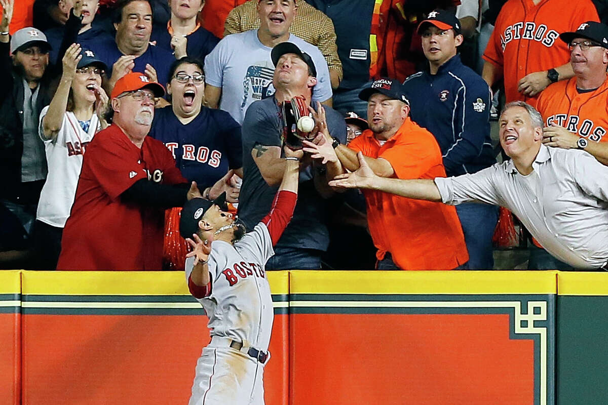 HOUSTON, TX - OCTOBER 17: A fan interferes with Mookie Betts #50 of the Boston Red Sox as he attempts to catch a ball hit by Jose Altuve #27 of the Houston Astros (not pictured) in the first inning during Game Four of the American League Championship Series at Minute Maid Park on October 17, 2018 in Houston, Texas.