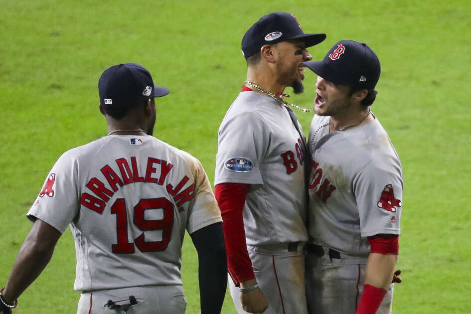 Red Sox left fielder Andrew Benintendi (right) celebrates with teammates Mookie Betts and Jackie Bradley Jr. after game-ending diving catch on Astros star Alex Bregman's bases-loaded line drive to win Game 4 of the American League Championship Series on Wednesday at Minute Maid Park.