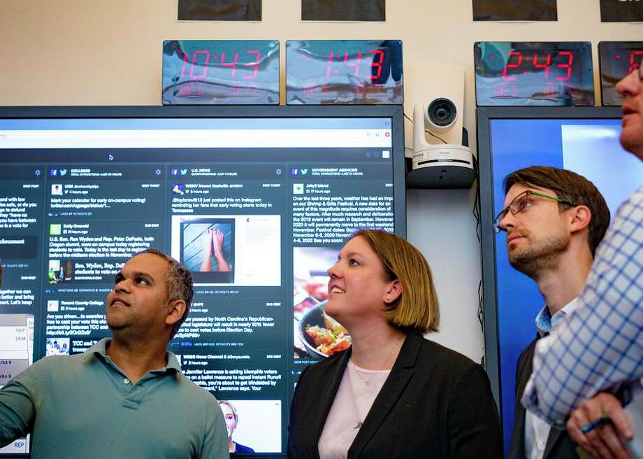 Samidh Chakrabarti, director of elections and civic engagement, Katie Harbath, global politics and government outreach director, and Nathaniel Gleicher, cyber security policy, observe live data streams from inside the Facebook election war room. Photo: CBSI/CNET