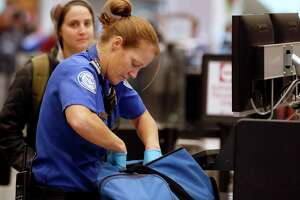 A Transportation Security Administration officer checks a traveler's bag at a screening location at Salt Lake City International Airport in Salt Lake City, Utah, on Dec. 23, 2016.