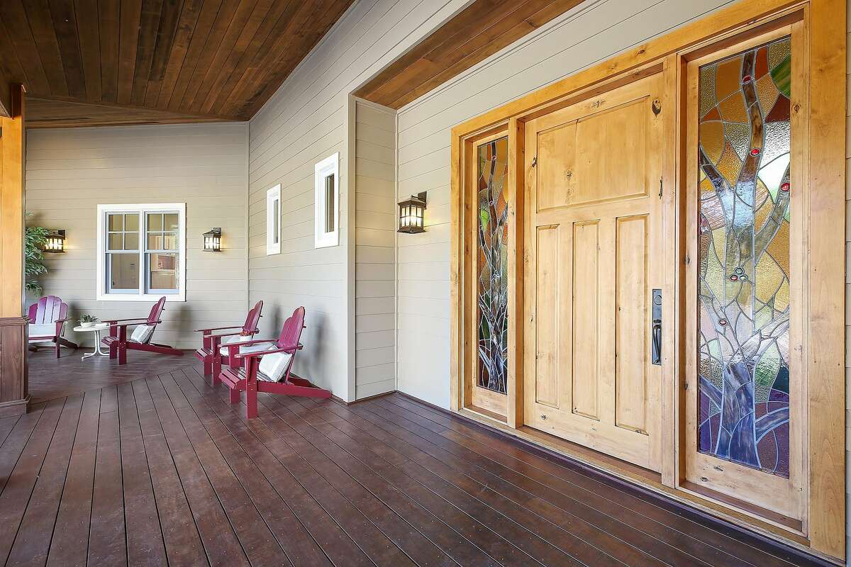 Stained glass windows stand beside the front door as a covered deck stretches before the Sonoma home.